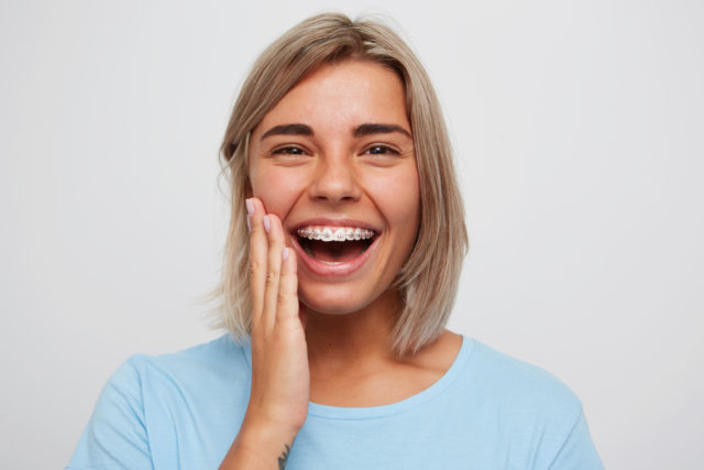 Cheerful beautiful young woman with blonde hair and braces on teeth laughing and touching her face by hand isolated over white background