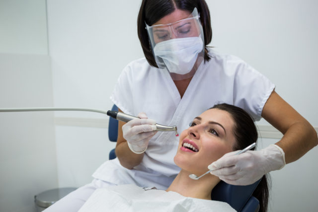 Dentist examining a female patient with tools at dental clinic